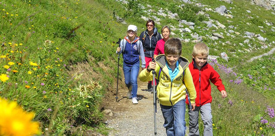Kinder wandern mit ihren Eltern auf einem Wanderweg