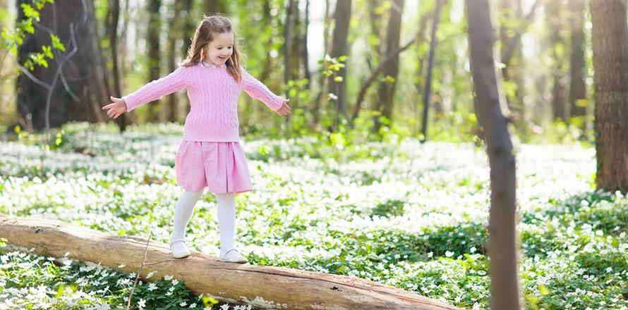 Ein Mädchen mit rosafarbenen Kleid balanciert auf einem Baumstamm in einem Wald im Frühlung