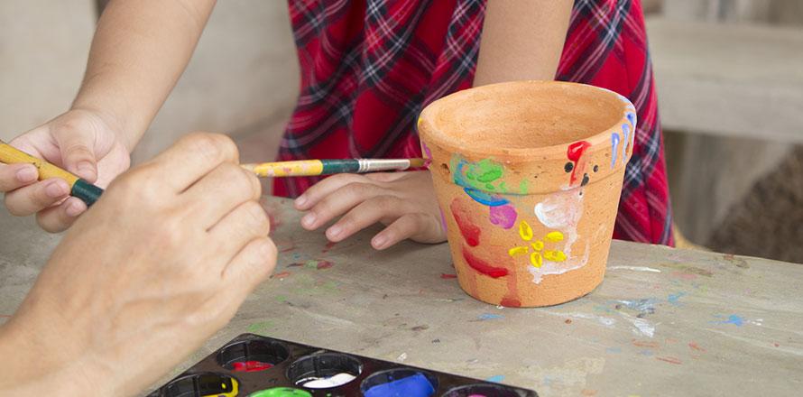 Ausschnitt von Kinderhänden, die Keramik-Blumentöpfe bunt bemalen
