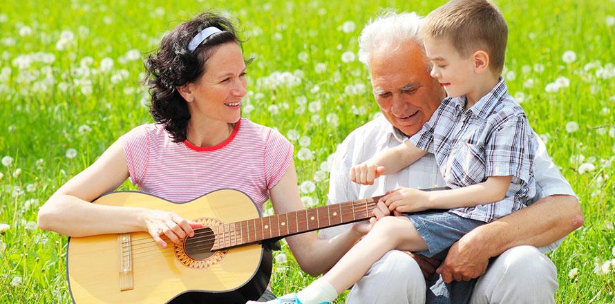 Mutter mit Gitarre auf einer Wiese, rechts daneben Großvater mit kleinem Jungen auf dem Schoß