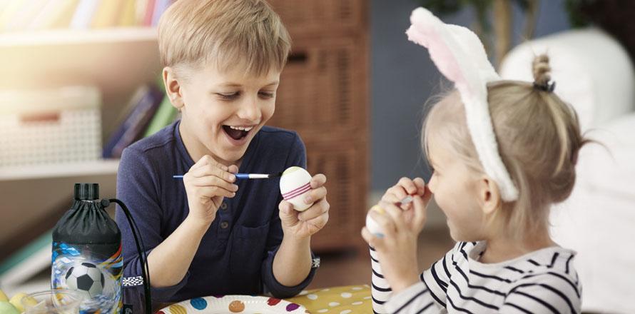 Zwei Kinder bemalen Ostereier an einem Tisch
